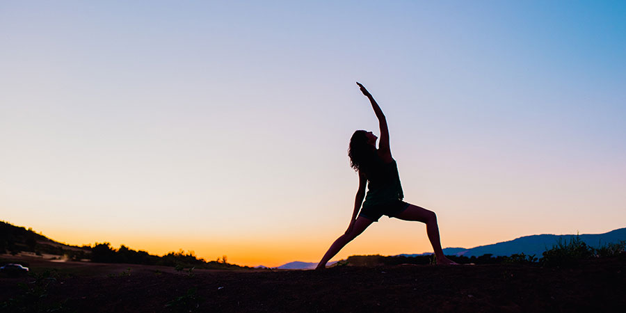 woman practices reverse warrior pose at sunrise