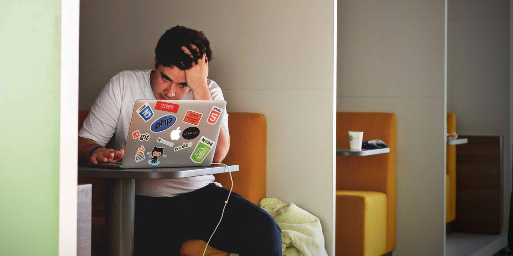 man staring at laptop looking distressed