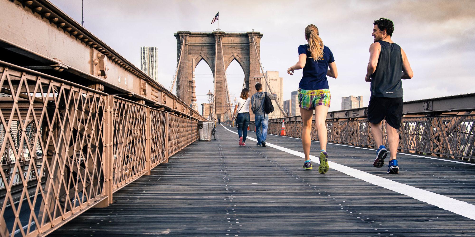 two people walking across a bridge