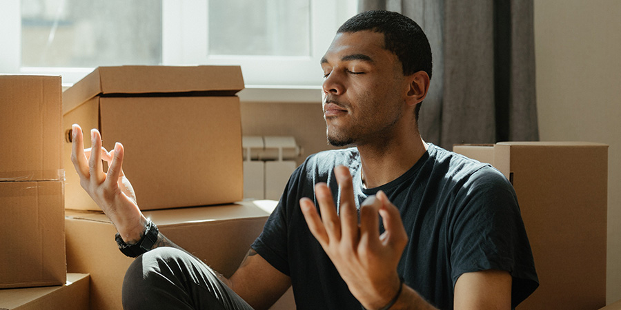 Man meditates near boxes