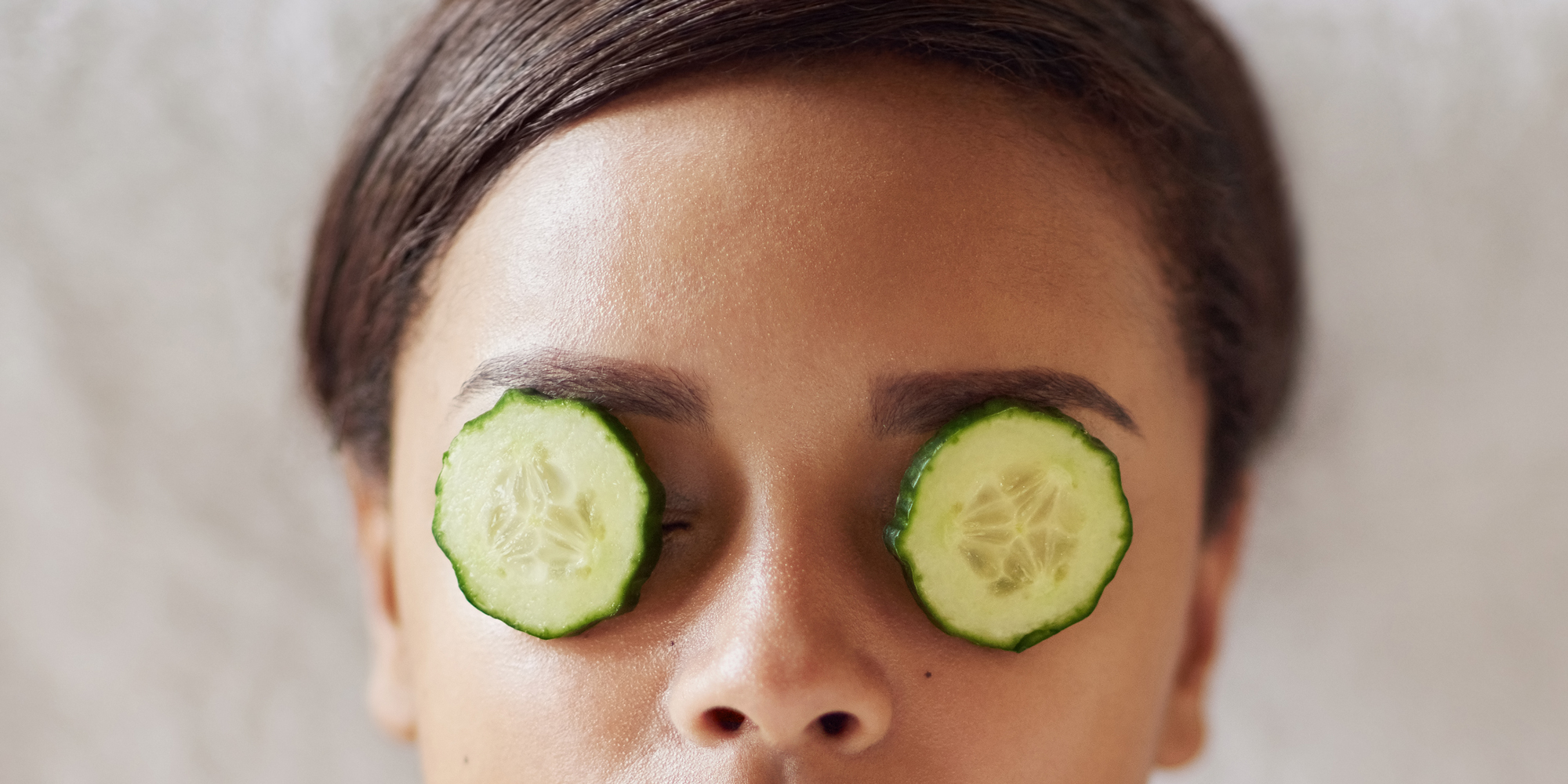 cucumers on woman's eyes