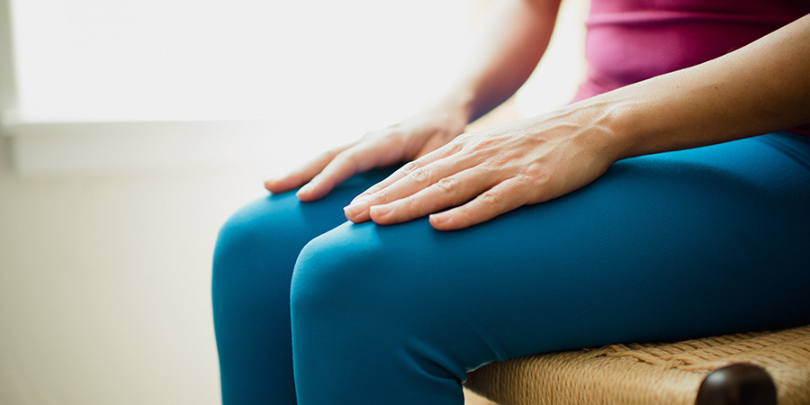 Woman meditating with hands resting atop her knees
