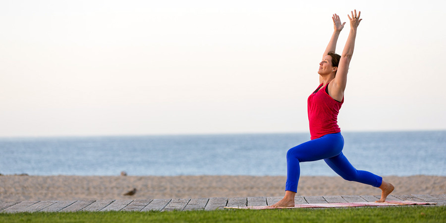 Banyan Ambassador Kathryn Templeton practices Warrior I from the Sun Salutation sequence on the beach