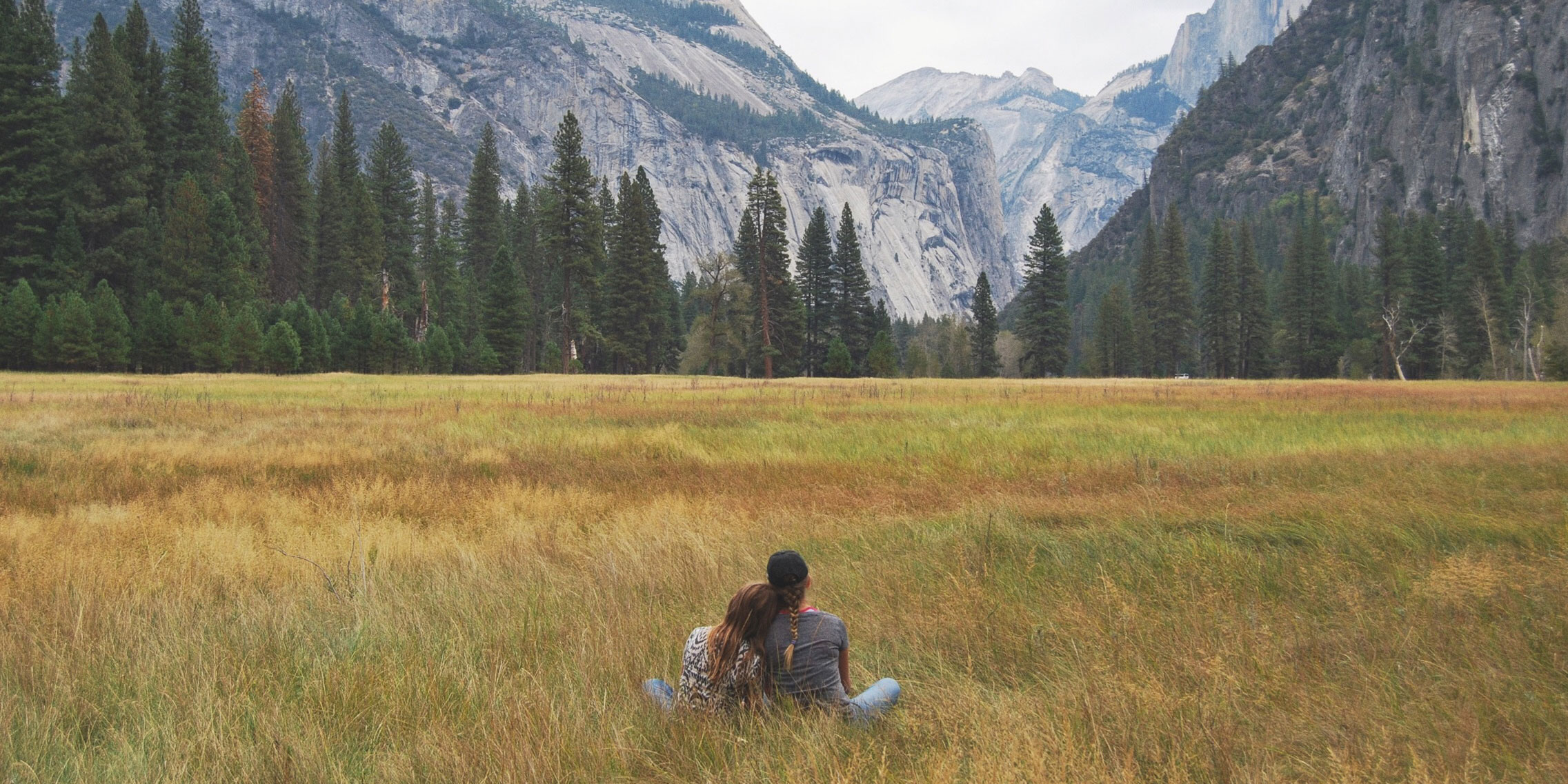two people sitting in field
