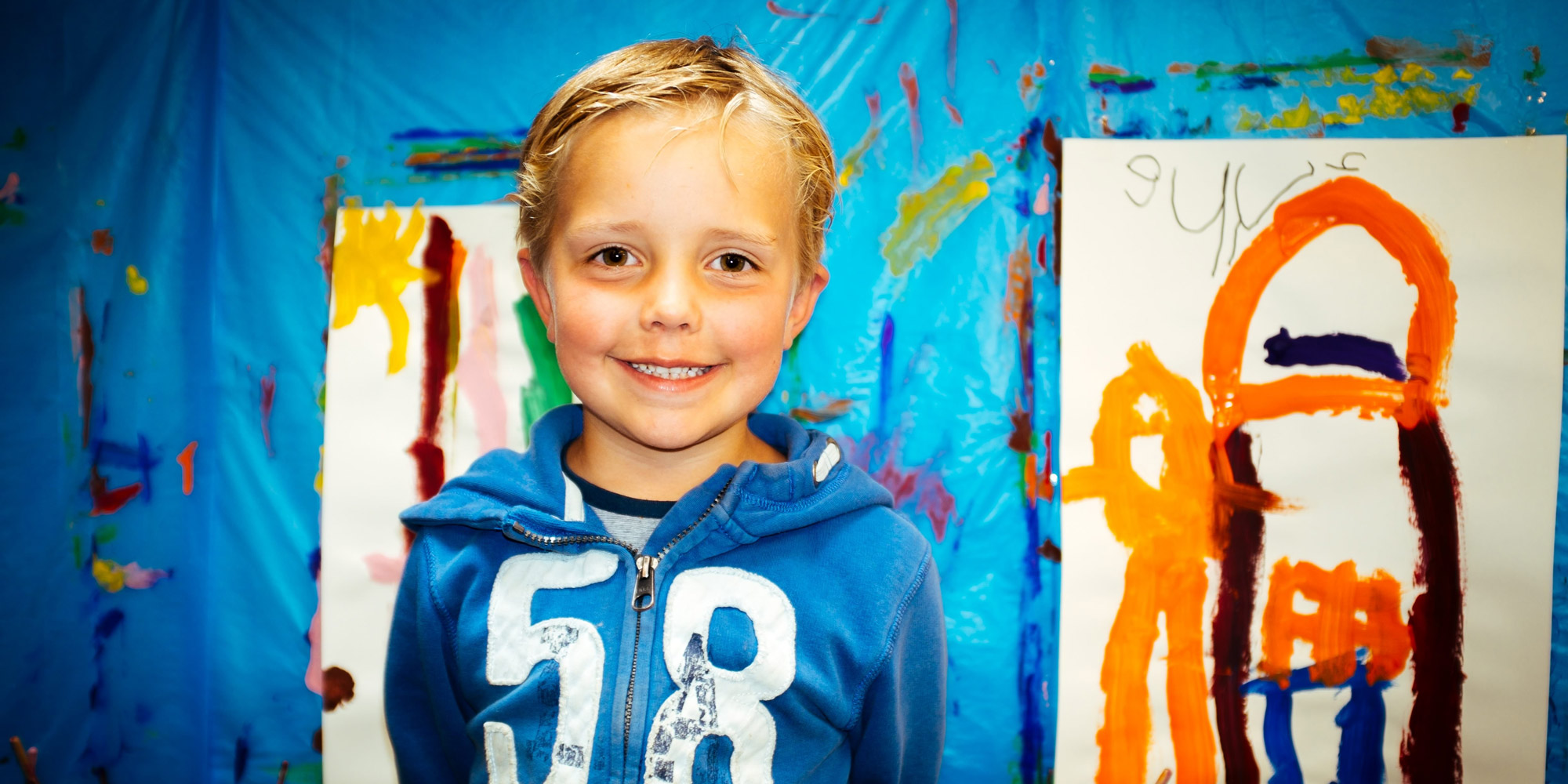young boy in front of finger paintings
