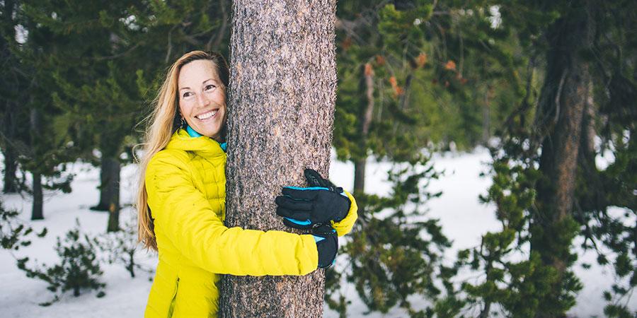 Banyan friend Heather hugs a tree on a winter day