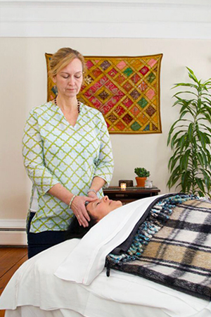 Banyan Ambassador, Allison Morse giving panchakarma treatment in her office.