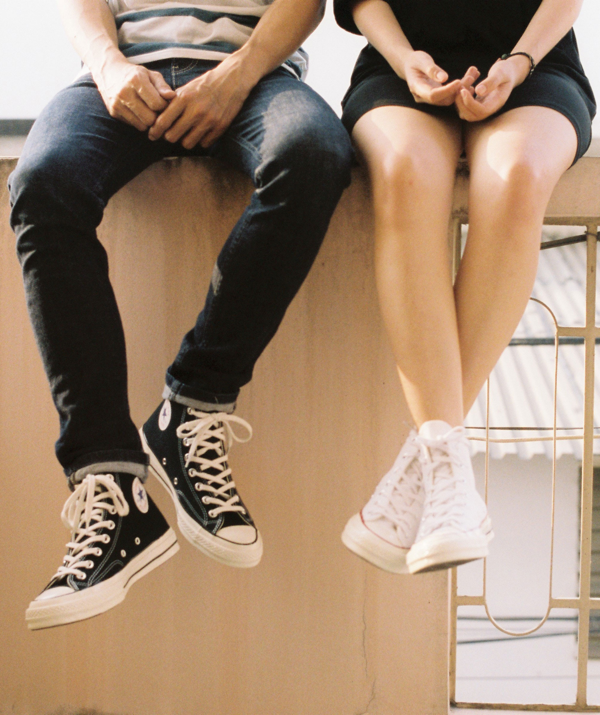 Legs in sneakers dangling from high surface as couple talks.