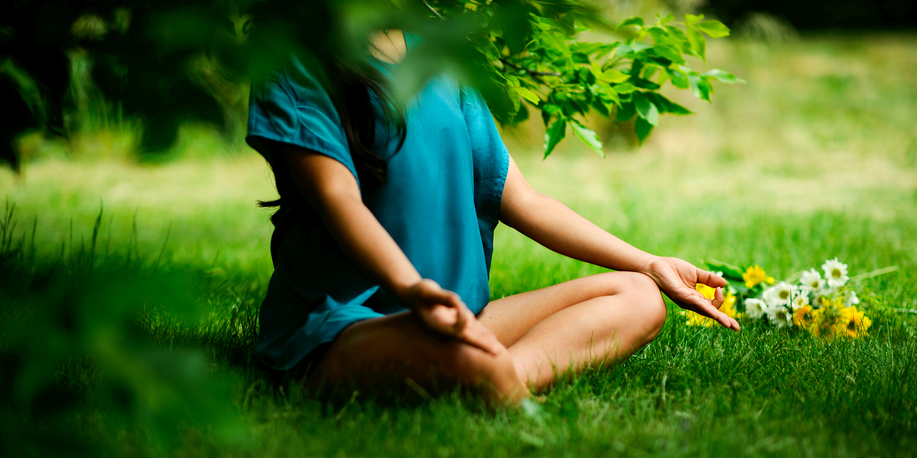 Woman meditating under tree.