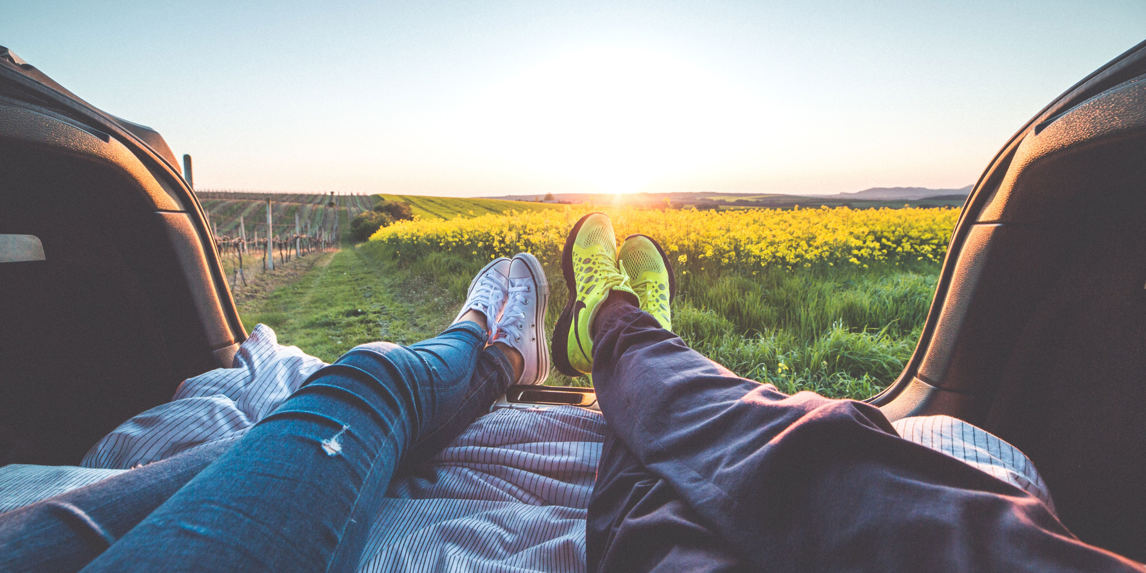 Couple's legs in jeans and sneakers outstretched in back of car looking out at a field of yellow flowers.
