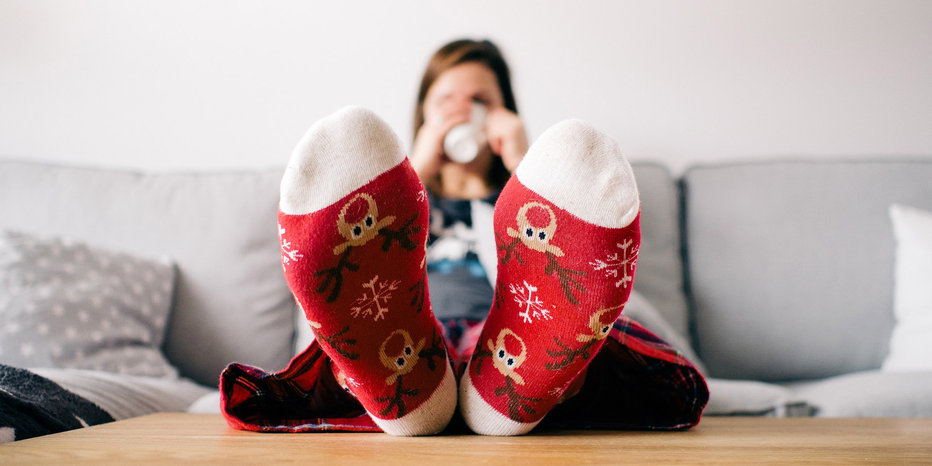 woman on couch wearing reindeer socks