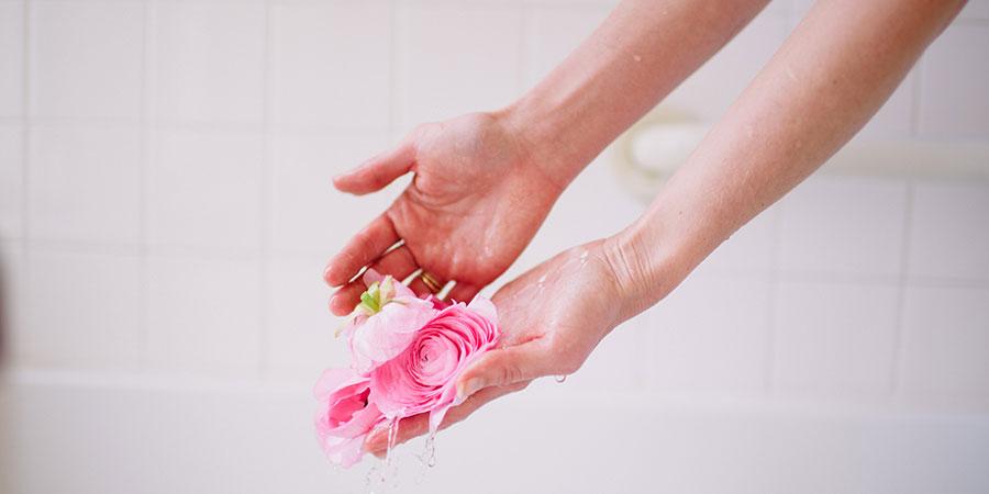 Hands sprinkling flower petals into a bath