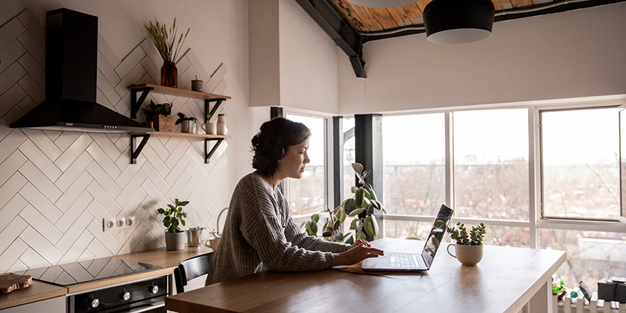 Woman wearing headphones working from a laptop in kitchen